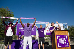 (From left to right) Dr. Nicholas Nissen, Michael Downs and Dr. Rick Selby take part in the PurpleStride Los Angeles ribbon ceremony accompanied by event emcee, Lisa Kennedy Montgomery.