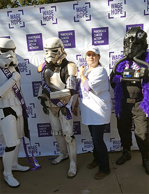 Pancreatic cancer survivor stands with people dressed in white Stormtroopers armor at fundraiser walk