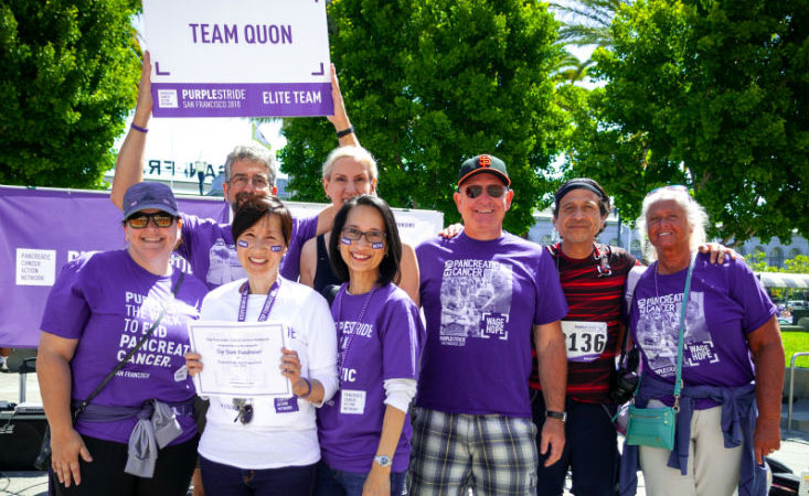 16-year pancreatic cancer survivor with team members of 5K walk event smile as top fundraisers