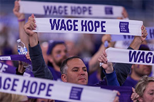 "A group of pancreatic cancer supporters stand united holding banners that read ""Wage Hope"""