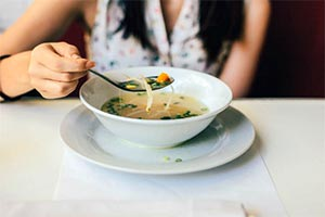 A bowl of soup filled with vegetables provides a flavorful, low-fat, fast-food option