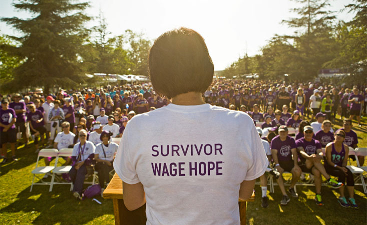 """A woman speaks for the pancreatic cancer cause in a shirt that reads """"Survivor: Demand Better"""""""