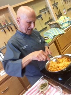Chef and pancreatic cancer survivor prepares a meal and takes enzymes to manage symptoms