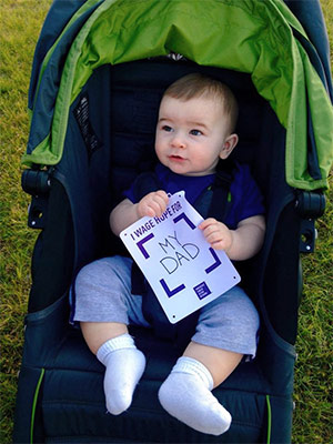 "Baby boy holds ""I Wage Hope for My Dad"" sign at pancreatic cancer walk/run fundraiser"
