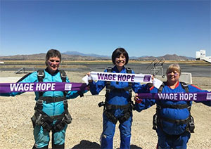 Three pancreatic cancer survivors hold Wage Hope banners before skydiving for the cause Marathon photo: Pancreatic cancer survivor holding medals from her Marathon runs