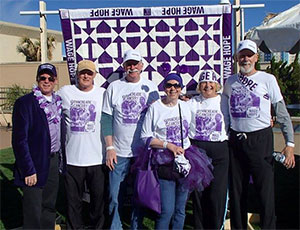 Pancreatic cancer survivors in front of quilt made by a survivor at PurpleStride Virginia Beach