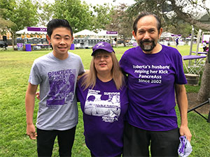 Teenage fundraiser stands with pancreatic cancer survivor and her husband at PurpleStride walk