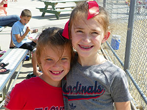Girls when they were younger together at a baseball tournament