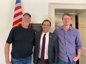 Husband and son of pancreatic cancer patient smile with Congressman Crow in his D.C. office.