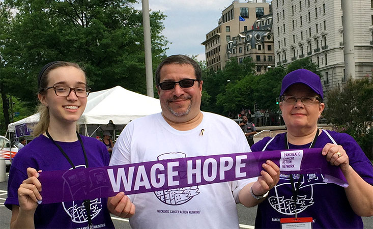 """Pancreatic cancer survivor holds """"Wage Hope"""" banner with his wife and daughter at PurpleStride"""