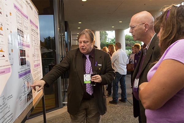 Pancreatic cancer researcher explains his scientific poster to PanCAN volunteers at conference