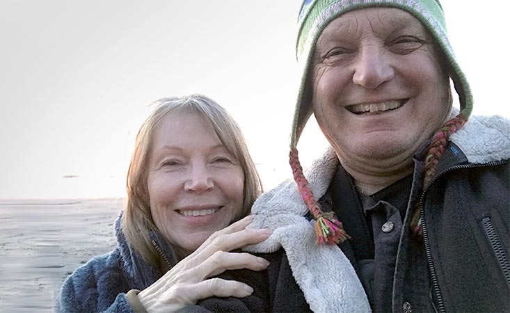 Stage 4 pancreatic cancer survivor smiling with her husband and caregiver