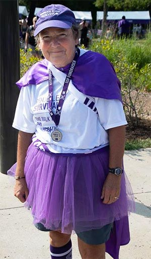 PanCAN volunteer at Louisville cancer walk wearing purple cape and top fundraiser medal