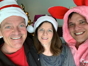 Husband and wife in their 50's with son in his 30's, in Santa Claus caps, smiling at the camera.